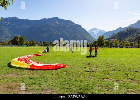 Switzerland, Interlaken, Hoehenmatte, 29 September 2019. View at the spectacular Jungfrau mountain range during a sunny day with paragliders standing - Stock Photo