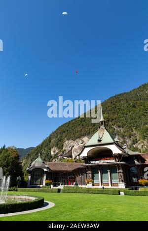 Switzerland, Interlaken, 29 September 2019. View at the historic casino building with paragliders flying in the clear blue sky. - Stock Photo