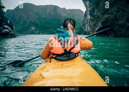 Girl kayaking on the seaside of Halong bay in Vietnam. Woman rowing oars in the boat. The view from the back. - Stock Photo