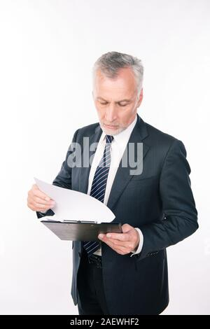 A portrait of aged focused man working with clipboard - Stock Photo