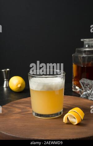 Whiskey sour cocktail - bourbon with lemon juice, sugar syrup and egg white in glass on wooden board on black. Vertical orientation. - Stock Photo