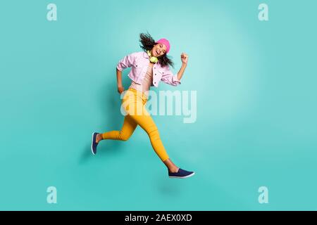 Full length body size photo of casual positive running jumping aspiring girl developing fast speed in yellow trousers striped t-shirt jacket pink - Stock Photo