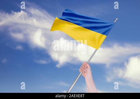 Female hand is waving Ukrainian Flag against blue sky with clouds. Realistic reflections and textures with high resolution. 3D rendering. - Stock Photo