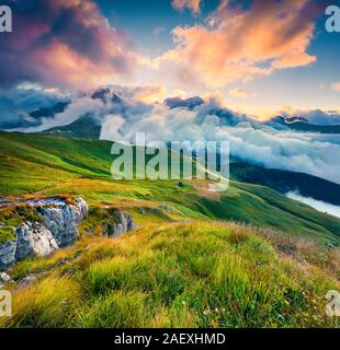 Few seconds before sunrise in the foggy Val di Fassa valley with passo Sella. National Park. Dolomites, South Tyrol, Italy, Europe. - Stock Photo