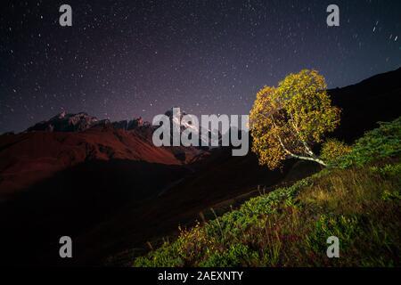 Night view of Ushba mountain with dark starry sky. Beautiful outdoor scene in the Caucasus mountains, Upper Svaneti, Europe. - Stock Photo