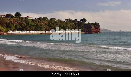 Goodrington beach, and beach huts beneath Roundham Head, Torbay, Devon. - Stock Photo