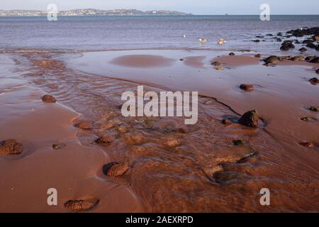 A shallow stream flowing into the sea over Broadsands beach at low tide. - Stock Photo