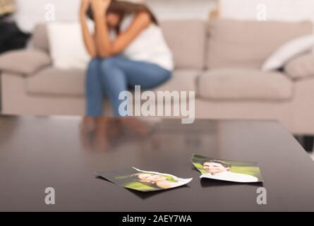 Unrecognizable Woman Crying After Breakup With Ex Boyfriend Sitting On Sofa Indoor, Torn Apart Photo Of Couple Lying On Table - Stock Photo