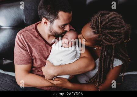 Multiracial parents kissing newborn baby wrapped in white blanket