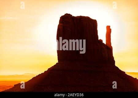 View closeup of one famous mesa butte mitten formations with red orange rock color on horizon in Monument Valley canyons during sunrise in Arizona - Stock Photo