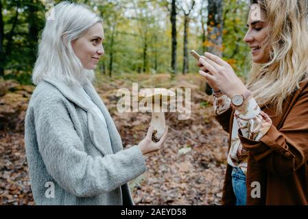Two young women taking snapshot of a mushroom in a forest
