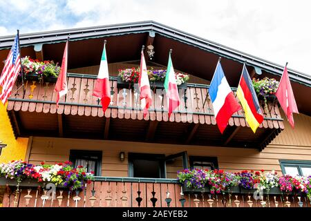 Vail Swiss style resort town in Colorado with low angle view of many flags on Gore Creek drive exterior of house balcony