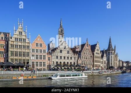 Sightseeing boat and tourists on quay along river Lys with view over guildhalls at the Graslei / Grass Lane in the city Ghent, East Flanders, Belgium - Stock Photo