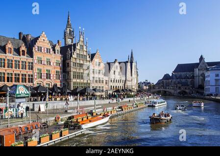 Sightseeing boats with tourists on the river Lys with view over guildhalls at the Graslei / Grass Lane in the city Ghent, East Flanders, Belgium - Stock Photo