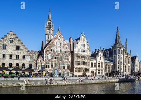 Tourists on quay along the river Lys / Leie and view over medieval guildhalls at the Graslei / Grass Lane in the city Ghent, East Flanders, Belgium - Stock Photo