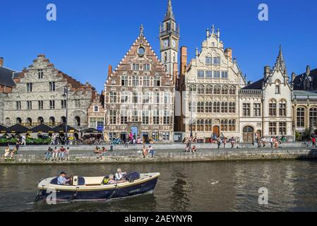 Motor boat with tourists on the river Lys with view over guildhalls at the Graslei / Grass Lane in the city Ghent / Gent, East Flanders, Belgium - Stock Photo