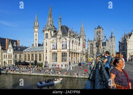 Sightseeing boat with tourists on the river Lys with view over guildhalls at the Graslei / Grass Lane in the city Ghent / Gent, East Flanders, Belgium - Stock Photo