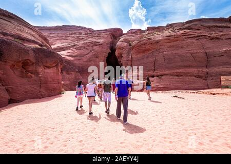 Page, USA - August 10, 2019: Navajo tribal tours people group entering Upper Antelope slot canyon in Arizona walking view - Stock Photo