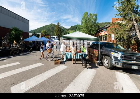 Aspen, USA - July 6, 2019: Vendors selling produce at stall stand in farmers market with people walking in outdoor summer street