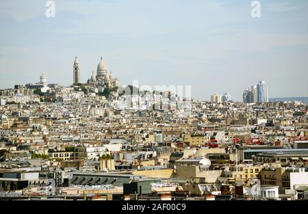 Sacre Coeur basilica and Chateau d'eau Montmartre on the hill, seen across the densely-built Paris cityscape from the top of the Arc de Triomphe