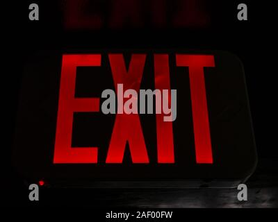 A bright red 'EXIT' sign. - Stock Photo