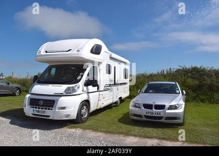 White spacious camper van and cars parked on the beach car park. - Stock Photo