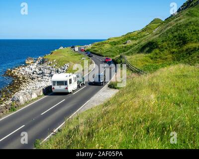 The eastern coast of Northern Ireland and Antrim Coast Road A2, a.k.a Causeway Coastal Route with cars. One of the most scenic coastal roads in Europe - Stock Photo