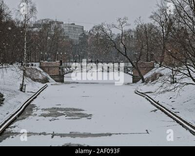 Pedestrians crossing the City Canal over a bridge in Downtown Riga on a snowy March day close to Easter - Stock Photo