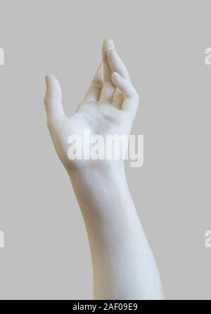 side view closeup of white stone marble statue hand reaching out to the heavens isolated on grey background - Stock Photo