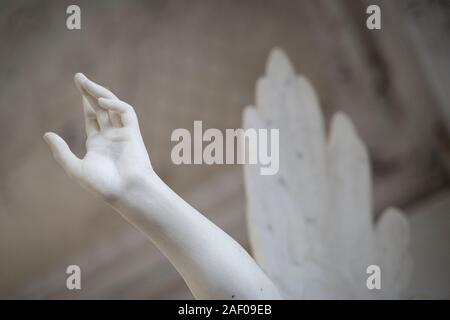 side view closeup of white stone marble angel statue hand reaching out to the heavens - Stock Photo