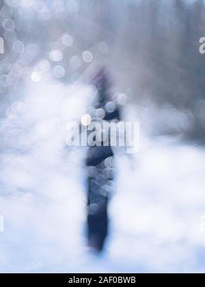 Walk through the winter forest. Silhouette of a lonely person in black walking on the road. - Stock Photo