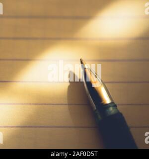 pen on notebook paper in a line, macro photo. - Stock Photo
