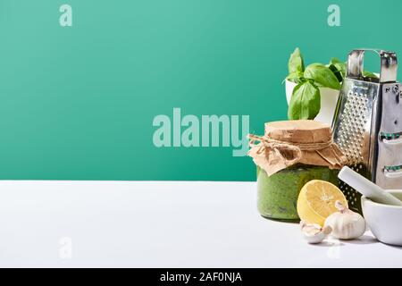 pesto sauce in jar near ingredients and grater on white table isolated on green - Stock Photo