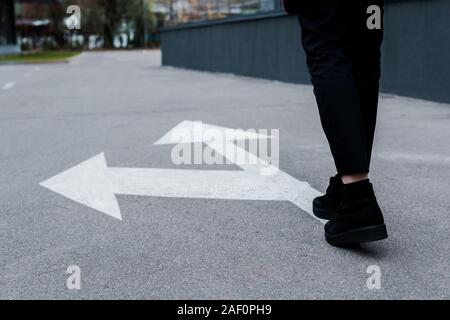 cropped view of woman walking near directional arrows on asphalt - Stock Photo
