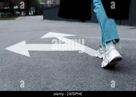cropped view of woman in jeans walking near directional arrows on asphalt - Stock Photo