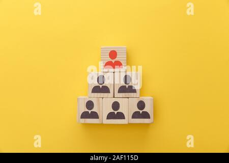 top view of pyramid of wooden cubes with logos on yellow background - Stock Photo