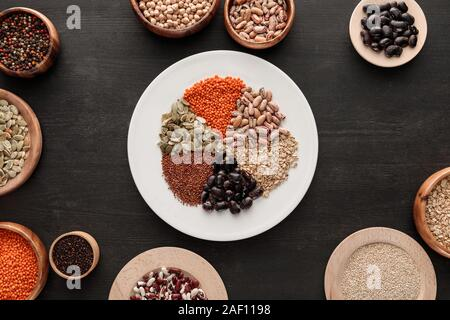 top view of white plate with various raw legumes and cereals near bowls on dark wooden surface - Stock Photo