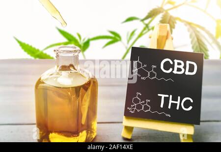 Cannabis oil in glass bottle and chalkboard with molecule drawing of THC and CBD on wooden table - Stock Photo