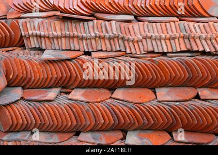 Closeup stack of traditional ceramic roof tiles used for covering rooftop of Thai temples - Stock Photo