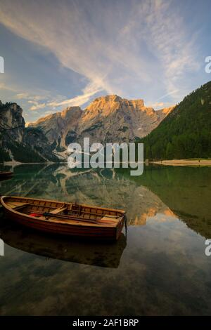 Boats and slip construction in Braies lake with crystal water in background of Seekofel mountain in Dolomites in morning, Italy Pragser Wildsee - Stock Photo