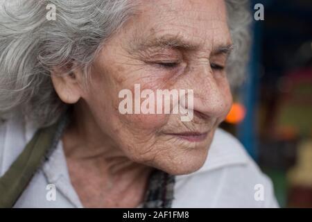 Porto Alegre, Rio Grande do Sul, Brazil - October 28, 2015: Senior Brazilian woman in a street market of Porto Alegre, closing her eyes against the wi - Stock Photo
