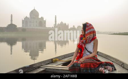 A woman watching sunset over Taj Mahal (Agra, India) from a wooden boat. - Stock Photo