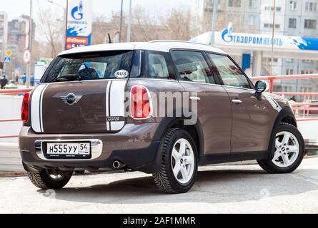 Novosibirsk, Russia - 06.26.2019: An expensive car, a female model of a mini cooper countryman beige and gold color and a white roof polished and shin - Stock Photo
