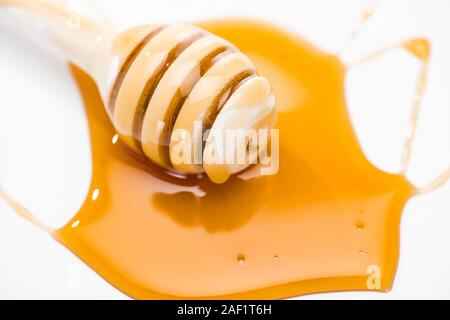 puddle of honey and wooden honey dipper isolated on white - Stock Photo