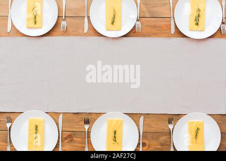 White plate's and yellow napkins. Festive table set for six people. Wooden background top view mock-up - Stock Photo