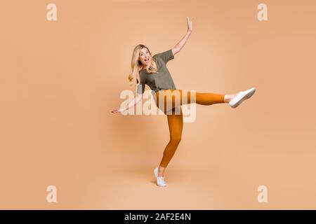 Full length body size turned photo of cheerful positive cute charming nice mature energetic woman in yellow green pants trousers expressing excitement - Stock Photo