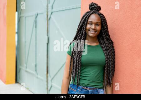 Beautiful african american young adult woman with amazing hairstyle outdoor in summer in city