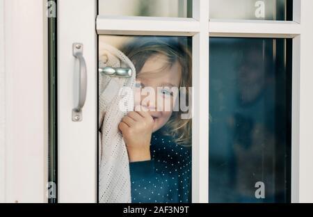 young girl looking through a door window smiling looking happy - Stock Photo