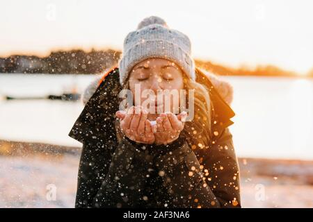 Woman blowing golden snow at sunset in winter