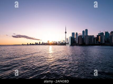 View of CN Tower and Toronto skyline from Toronto Islands Park at sunset. - Stock Photo